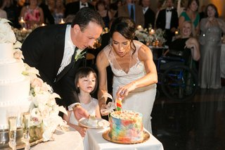bride-and-groom-cut-rainbow-cake-for-daughter