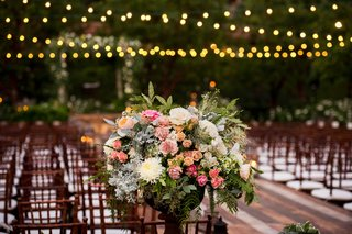 ceremony-space-decorated-with-strings-of-lights-over-wooden-chairs-and-pink-white-orange-florals
