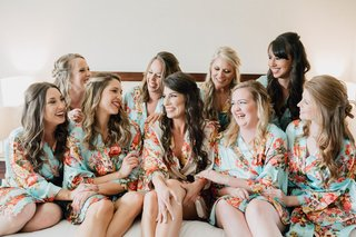 wedding-party-bridesmaids-on-bed-in-matching-silk-robes-mint-and-pink-flower-design-print-curled-hai