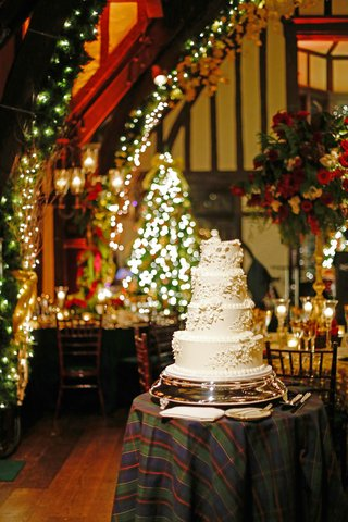 four-layer-white-wedding-cake-on-plaid-cake-table-in-reception-room-filled-with-christmas-decoration