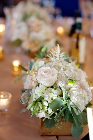 wedding-reception-table-with-white-hydrangeas-roses-and-greenery-in-a-rustic-wood-box