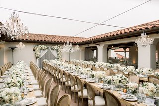 outdoor-wedding-reception-bacara-long-wood-tables-with-low-centerpieces-crystal-chandelier-overhead