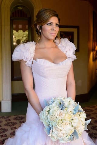 bride-in-blush-pink-wedding-dress-with-ruffle-bolero-and-skirt-carries-white-and-ivory-rose-bouquet