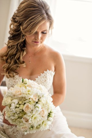 bride-in-ines-di-santo-strapless-wedding-dress-with-curled-hair-brought-to-one-side-side-bangs