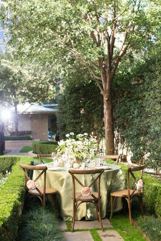 napa-woodlands-inspired-tablescape-greenery-in-a-garden-wooden-chairs-green-table-linens-outdoors