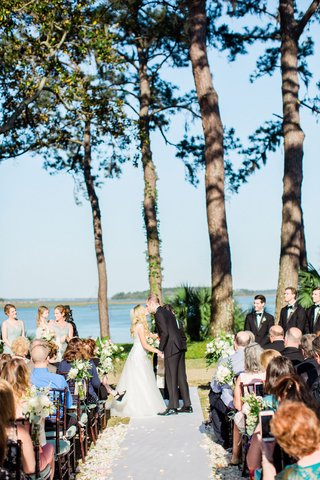 bride-and-groom-kiss-during-outdoor-wedding-ceremony-montage-palmetto-bluff-water-view-flower-petals