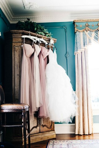 a-brides-tulle-ball-gown-hanging-next-to-bridesmaids-strapless-pink-dresses