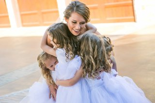 bride-smiles-while-holding-three-flower-girls-with-lavender-dresses-and-ringlets