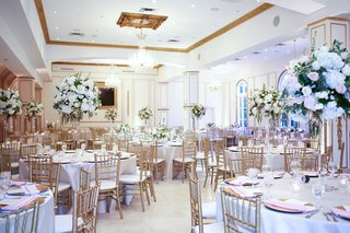 ballroom-reception-with-gold-details-round-tables-with-linens-gold-chairs-pink-napkins-tall-flowers