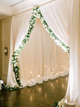 wedding-reception-ballroom-entrance-white-drapery-garland-of-greenery-candles-white-flowers