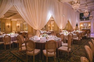 wedding-reception-drapery-ballroom-oval-back-wood-chairs-low-centerpiece-chandelier