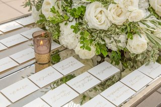 mirror-tabletop-with-gold-calligraphy-white-escort-cards-white-rose-flower-arrangement-greenery