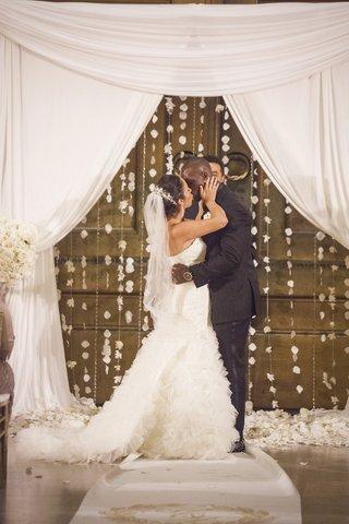 tennessee-titan-jason-mccourty-in-black-tuxedo-kisses-bride-in-mark-zunino-dress-at-ceremony