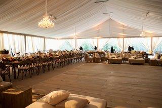 wooden-dance-floor-under-chandelier-in-middle-of-tented-wedding-space