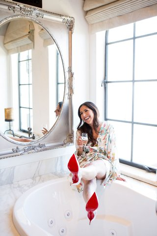 bride-in-flower-print-robe-getting-ready-in-bridal-suite-by-bathtub-in-louboutins-red-sole