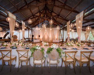 wedding-reception-head-table-over-dance-floor-orb-pendant-twinkle-light-strands-cane-vineyard-chairs