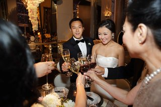 bride-in-strapless-wedding-dress-and-groom-in-tuxedo-toast-champagne-and-cheers-with-guests-drinking