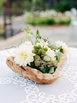 cocktail-hour-centerpiece-made-in-dirftwood-raw-wooden-bowl-with-white-flowers-and-greenery