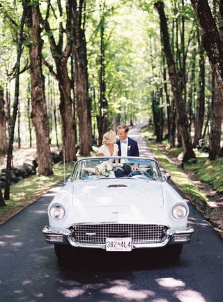 classic-baby-blue-historic-vehicle-on-small-road-in-forest-for-wedding-portraits