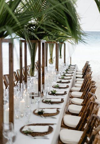 wedding-reception-long-white-table-palm-tree-centerpiece-wood-bamboo-chairs-ocean-bahamas