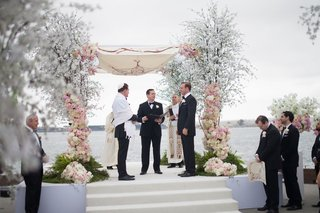 groom-in-yarmulke-and-tallit-with-other-groom-on-altar-officiant-cherry-blossom-trees-pink-flowers
