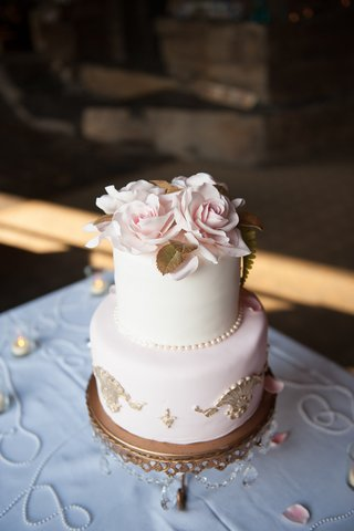 wedding-cake-with-pink-layer-and-white-layer-with-gold-details-and-flowers