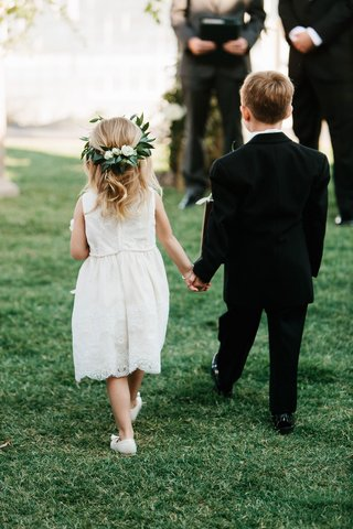 white-flower-girl-dress-with-leaf-flower-crown-holding-hands-with-ring-bearer-in-tuxedo-suit-grass