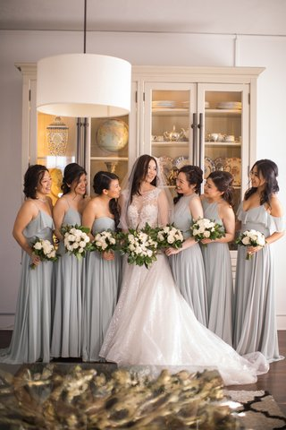 bridesmaids-in-pale-grey-blue-dresses-with-bride-in-berta-a-line-in-the-middle