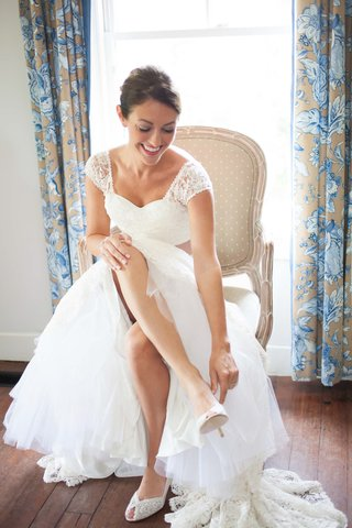 bride-in-a-lela-rose-lace-gown-puts-on-stuart-weitzman-heels-with-lace-details
