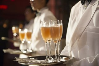 wedding-cocktail-hour-at-cipriani-wall-street-with-servers-in-white-blazers-tray-of-drinks
