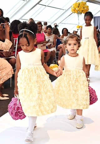 two-flower-girls-in-short-sleeve-pastel-yellow-dresses-carry-pomander-bouquets-of-light-purple-roses