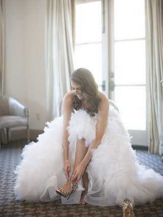 bride-in-bridal-suite-putting-on-lanvin-shoes-strappy-high-heel-sandals
