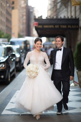 groom-in-tuxedo-and-bow-tie-with-patent-leather-shoes-and-brides-in-long-sleeve-dress-with-illusion