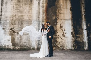 bride-in-off-shoulder-lace-wedding-dress-veil-flying-in-window-with-tuxedo-with-bow-tie