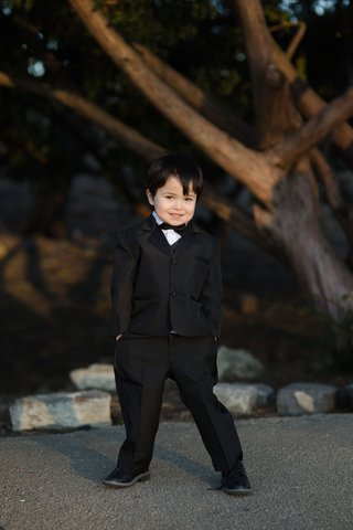 adorable-ring-bearer-in-black-tuxedo-with-his-hands-in-his-pockets