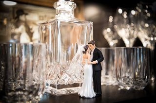 wedding-cake-topper-bride-in-dress-with-veil-groom-in-suit-next-to-bar-decanter-glasses