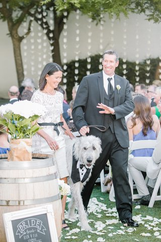 mother-of-the-bride-in-a-lace-byron-lars-dress-escorts-dog-with-father-of-the-bride-in-black-tuxedo