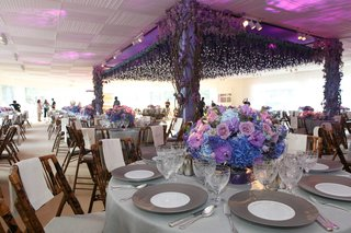 pink-purple-and-blue-flowers-in-low-table-arrangement-in-front-of-dance-floor-with-flower-structure