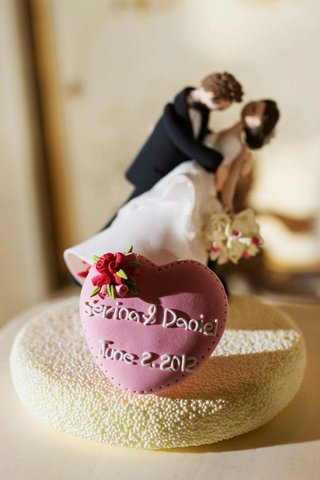 cake-topper-of-groom-figurine-dipping-bride-figurine-and-heart-with-bride-and-grooms-names