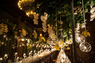 wedding-reception-tall-centerpiece-overhead-green-leaves-glass-globe-orbs-with-candles-and-yellow