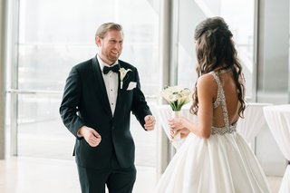 groom-in-tuxedo-bow-tie-and-calla-lily-boutonniere-reaction-to-bride-in-first-look-crystal-back-open