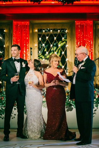 bride-and-groom-with-mother-of-bride-in-sparkling-red-sequin-gown-father-of-groom-toasts-holiday