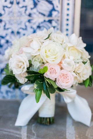 soft-wedding-bouquet-with-white-roses-pink-roses-and-green-leaves-wrapped-with-white-bow