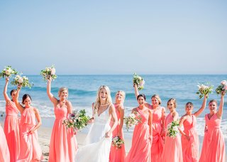wedding-portraits-of-bride-and-bridesmaids-mismatched-coral-pink-bridesmaid-dresses-ocean