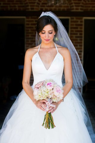 bride-in-white-tulle-ball-gown-with-plunging-halter-neckline-looking-down-at-blush-ivory-bouquet