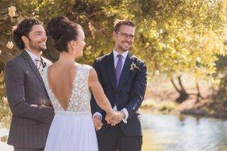 bride-in-mira-zwillinger-wedding-dress-from-carines-bridal-atelier-low-v-back-holding-hands-groom