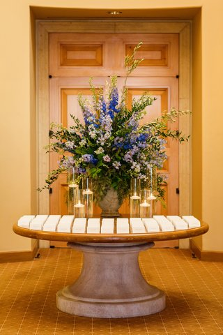 escort-card-table-with-large-display-of-bright-blue-and-light-periwinkle-flowers-floating-candles