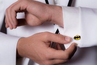 wedding-guest-in-white-tuxedo-jacket-wears-batman-logo-cuff-link-with-white-shirt