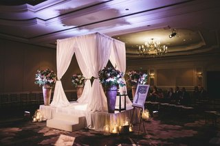 white-curtain-chuppah-with-large-vases-full-of-flowers-at-each-corner