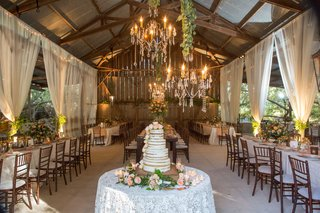 barn-wedding-reception-with-elegant-design-white-drapery-linens-naked-cake-chandelier-greenery